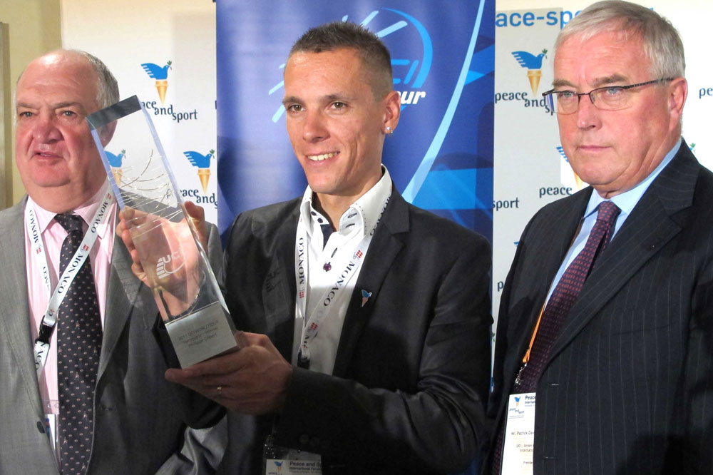 Philippe Gilbert reçoit le trophée de l'UCI WorldTour entre Jean-François Pescheux et Pat McQuaid
