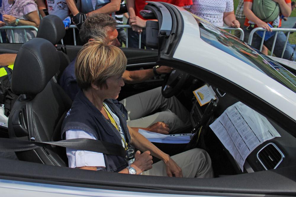Depuis sa place dans le cabriolet, Florence Pommerie veille sur le peloton