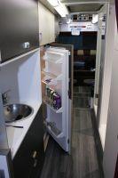 Le réfrigérateur, l'espace cuisine et les deux douches se situent au coeur du bus