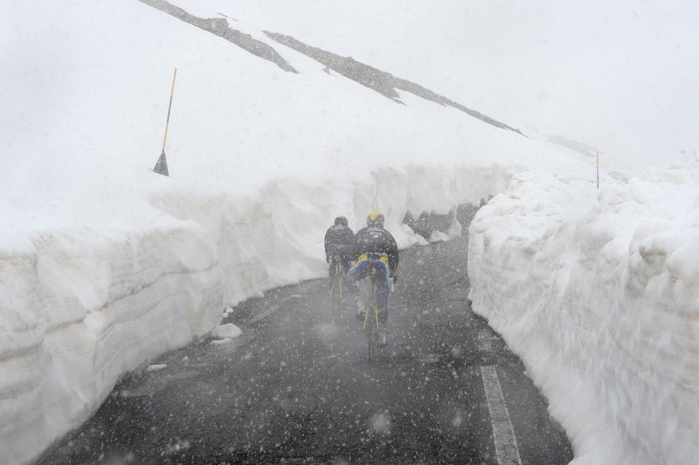 Image saisissante d'un peloton avançant entre deux murs de neige dans le Gavia